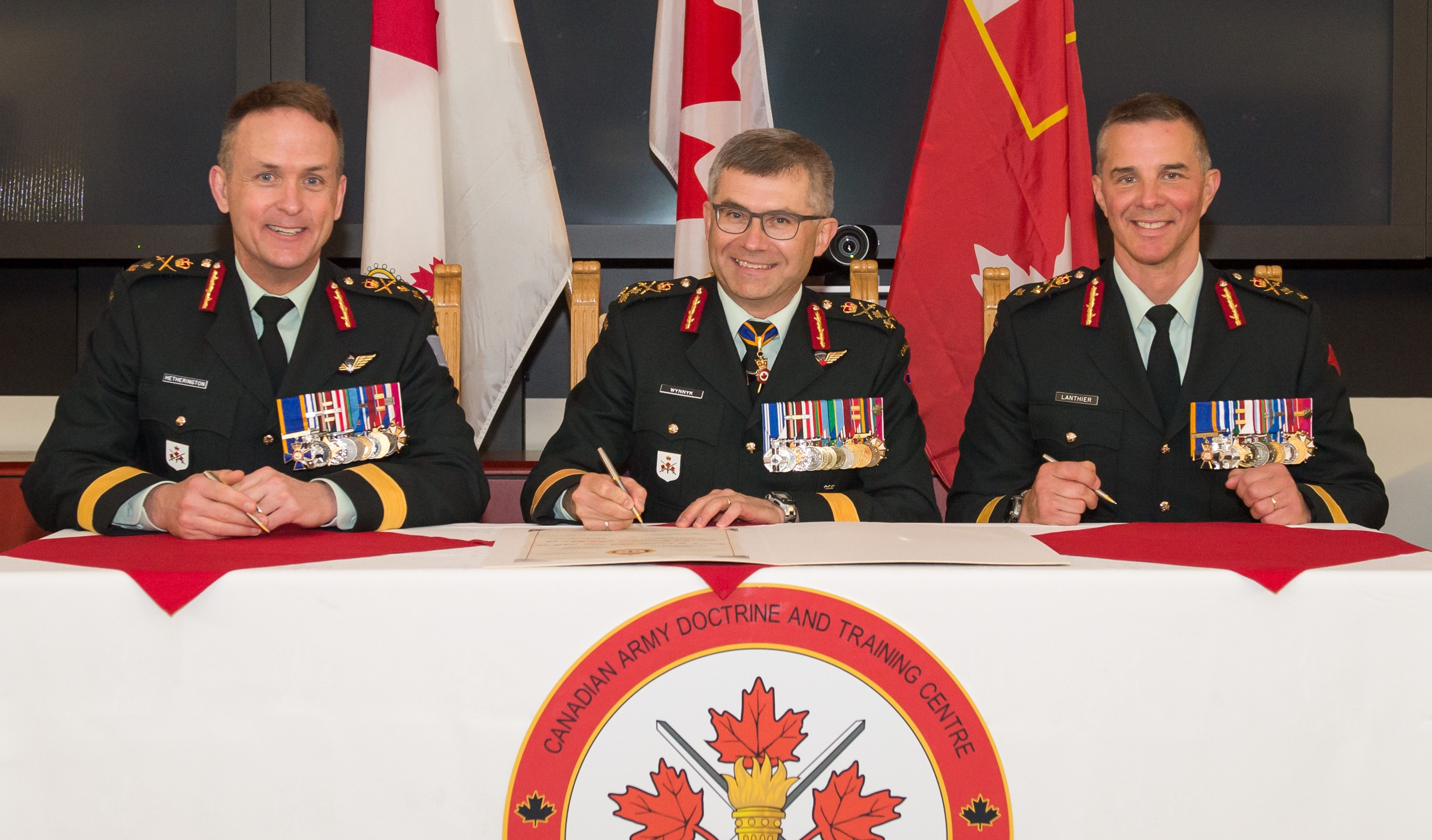 Major-General Simon Hetherington (left) assumes command of the Canadian Army Doctrine and Training Centre from Major-General Jean-Marc Lanthier (right) at Fort Frontenac, Kingston, on 26 April 2017. The ceremony is presided by Lieutenant-General Paul Wynnyk (centre), Commander Canadian Army.