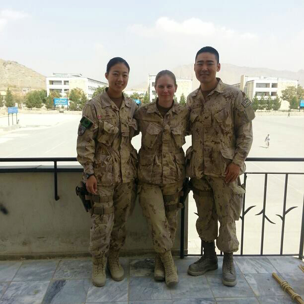 Captain Matthew Hou, Logistics Mentor (right), stands with Sergeant Nicole Taylor, Intelligence Mentor (centre) and Captain Sylvia Jeon, Logistics Mentor (left) on the balcony of the Kabul Military Training Center in Kabul, Afghanistan on 2013 after observing a graduation parade.  