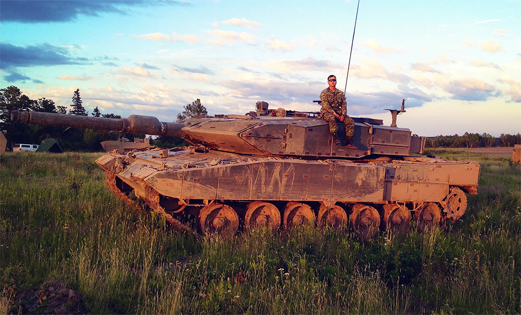 Captain Hyunjoon (Dave) Jung (then Lieutenant) in the summer of 2014, taking a break atop a Leopard 2A4M tank during his Tank Troop Leader course in the 5th Canadian Division Support Base Gagetown training area, New Brunswick. 