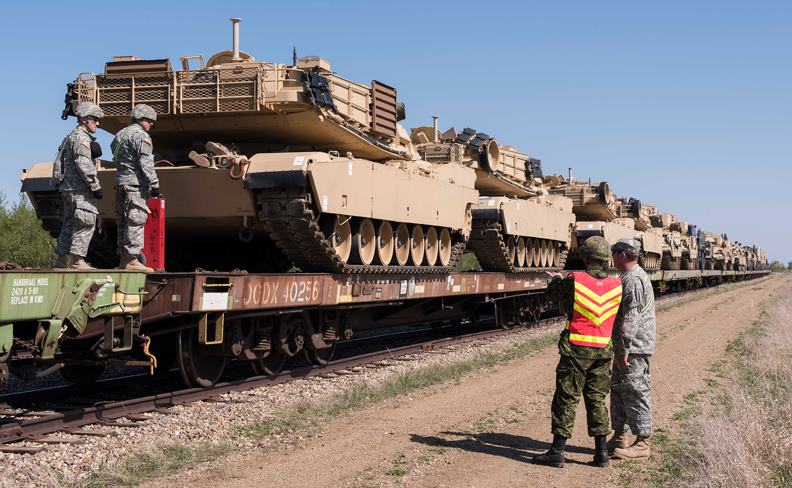 United States Army M1A2 Abrams Main Battle Tanks prepare to be offloaded from a train at Canadian Forces Base/Area Support Unit Wainwright, Alberta during Exercise MAPLE RESOLVE on May 11, 2017. Moving equipment is just one of the challenges of planning the Canadian Army's largest annual exercise. Photo: Sergeant JF Lauzé, 4th Canadian Division Support Base Petawawa. ©2017 DND/MDN Canada.