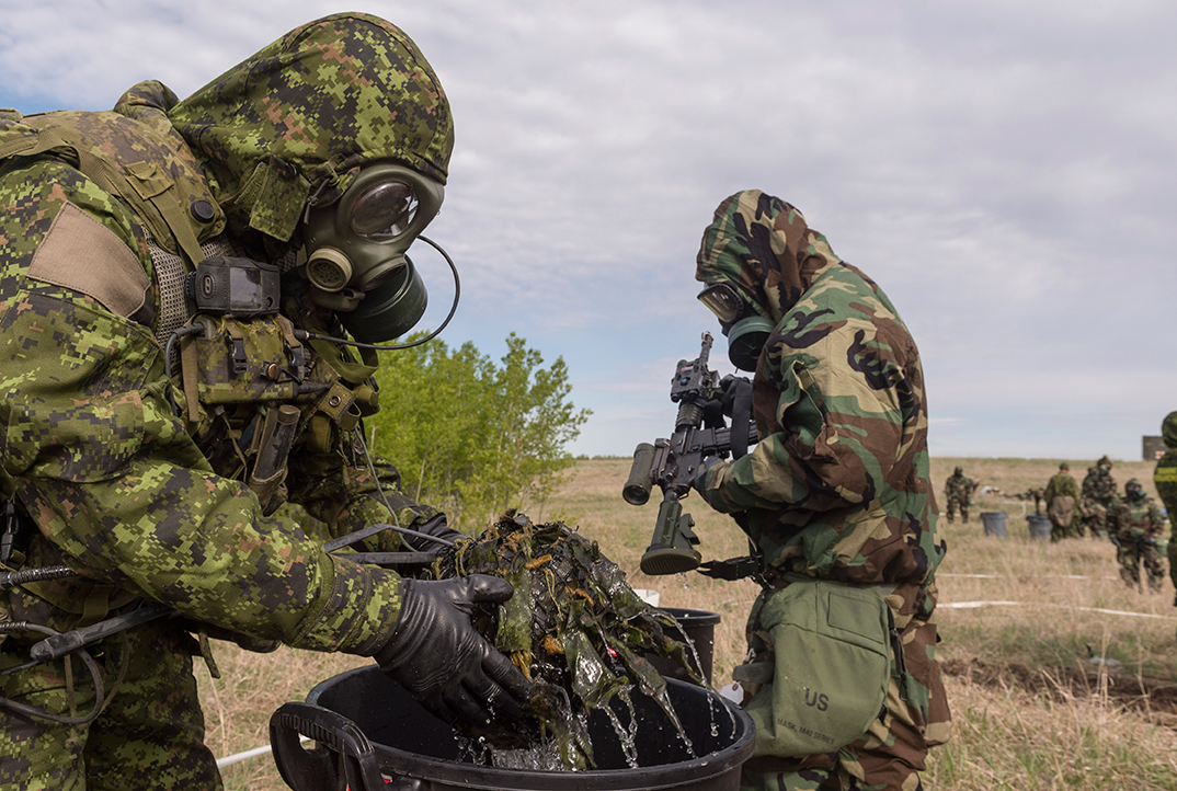 Soldiers of 1st Battalion The Royal Canadian Regiment and United States Army soldiers from 50th Chemical Company wash contaminated equipment at a Chemical Biological Radioactive Nuclear decontamination site during Exercise MAPLE RESOLVE on May 18, 2017. Lieutenant Colonel James L'Heureux of the Canadian Manoeuvre Training Centre says Canadian troops and their allies are working well together and sharing valuable knowledge during the exercise. Photo: Sergeant JF Lauzé, 4th Canadian Division Support Base Petawawa. ©2017 DND/MDN Canada.
