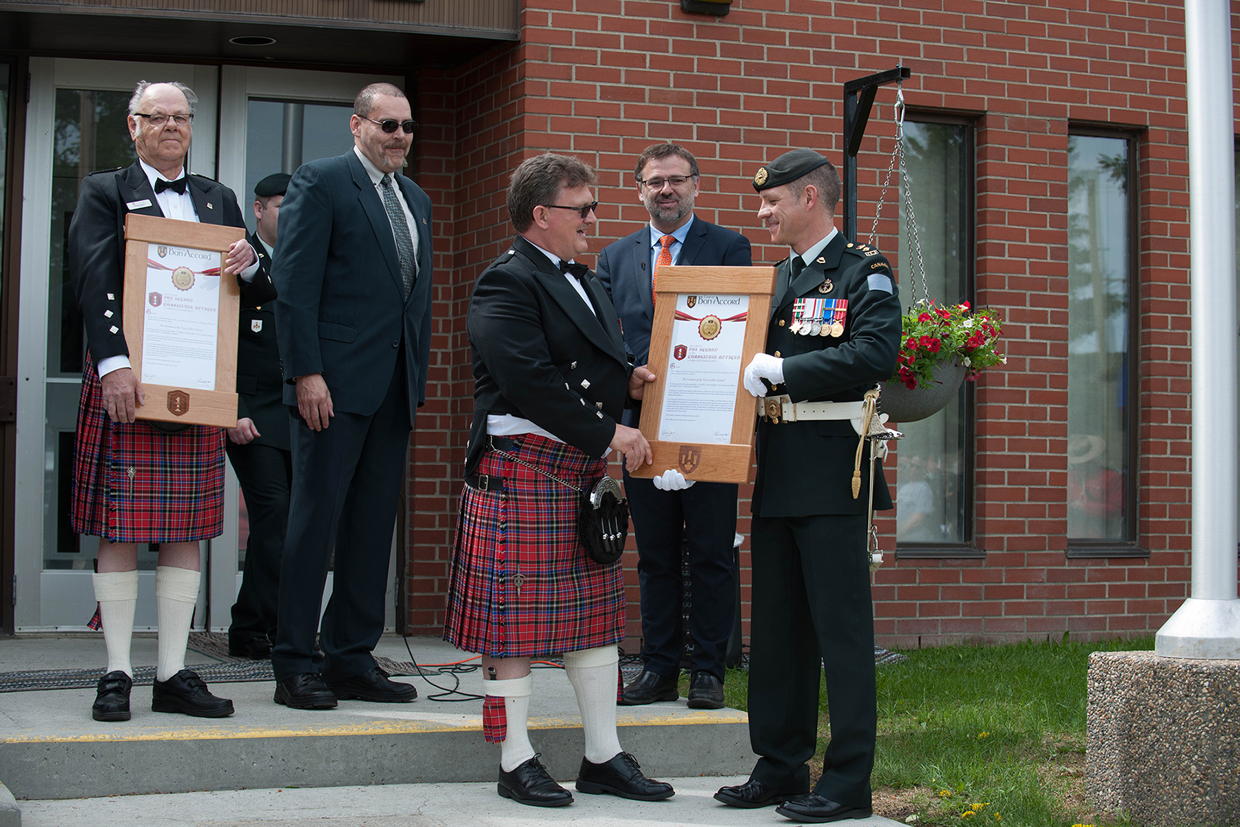 Mayor Randy Boyd (left) presents Lieutenant-Colonel Ryan Smith, Commanding Officer of 1 Combat Engineer Regiment (1 CER), with a scroll granting 1 CER the Freedom of the City in Bon Accord, Alberta on June 3, 2017.