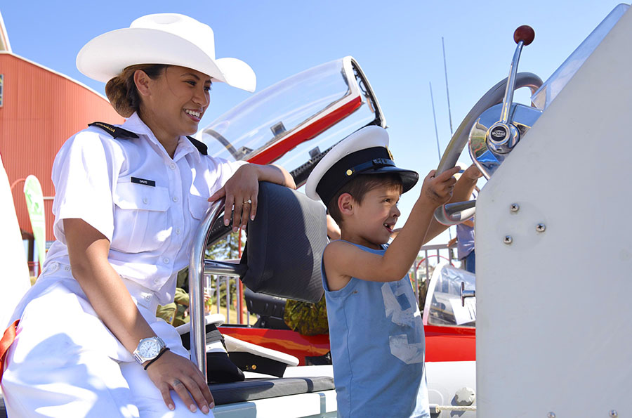A Navy member helps a little sailor get ready for the high seas