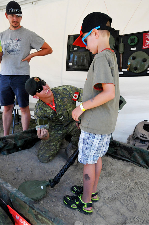 Corporal Tyler Graves of 41 Combat Engineer Regiment, shows a visitor what he found in the sand using the metal detector during a minefield clearing demonstration at the military display set up on the Calgary Stampede grounds from July 7 to 16, 2017