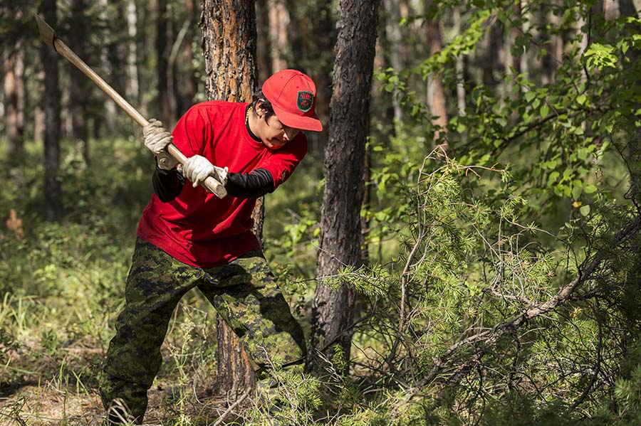 Private Malcom Miqwi, a member of 1 Canadian Ranger Patrol Group, cuts a fallen tree, as part of the fire control training in Camp Fort Smith, Northwest Territories during Operation NANOOK on August 24, 2015.  