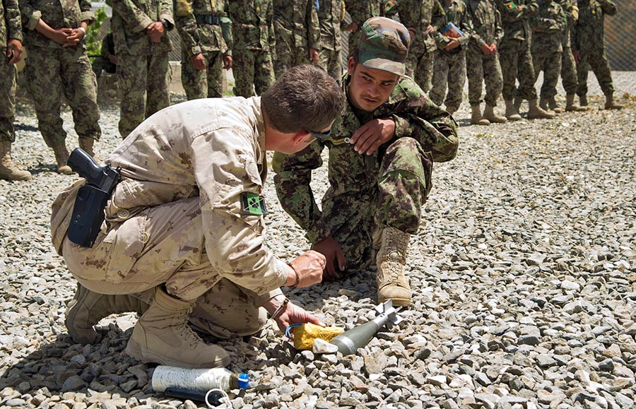 Warrant Officer Tim MacCormac demonstrates how to dispose of unexploded ordnance during a class with Afghan National Army soldiers in June, 2011. 
