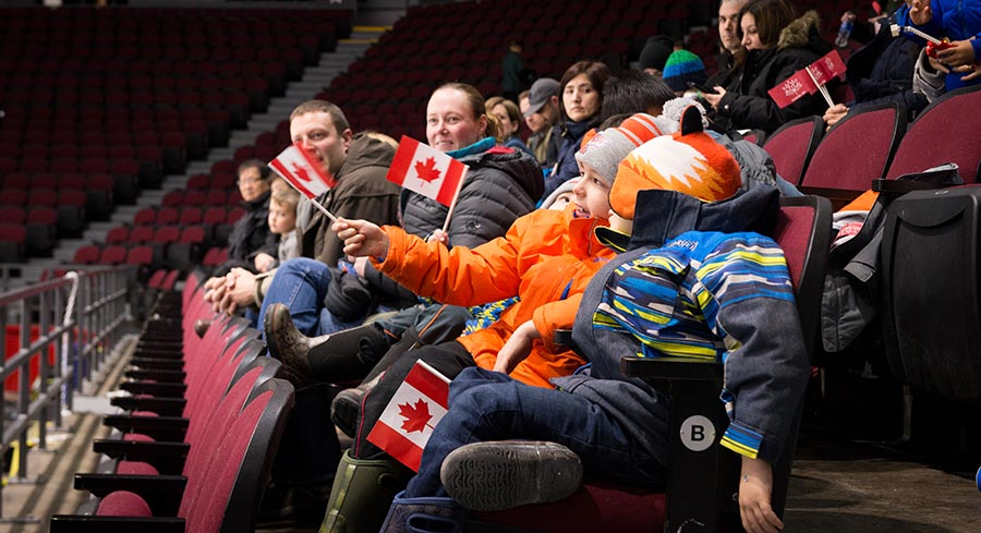 Young fans wave their flags while taking in the action at the TD Place in Ottawa.