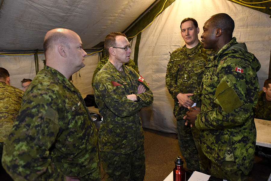 Captain Felix Odartey-Wellington (R), a Public Affairs Officer with 36 Canadian Brigade Group, speaks with Brigadier-General Derek Macaulay, Commander, 5th Canadian Division, and 36 Territorial Battalion Group Commander, Lieutenant-Colonel Shane Gallant during  Exercise STAGED RESPONSE 2017 in Pictou, Nova Scotia on May 6, 2017. 