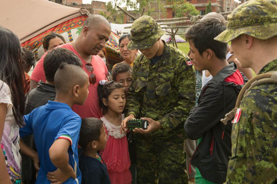 A soldier from the Canadian Army Information Activities Task Force, which is part of the Canadian Combat Support Brigade, demonstrates equipment for community members while on deployment with the Disaster Assistance Response Team (DART) in Nepal in 2015. © DND/MND 2015.