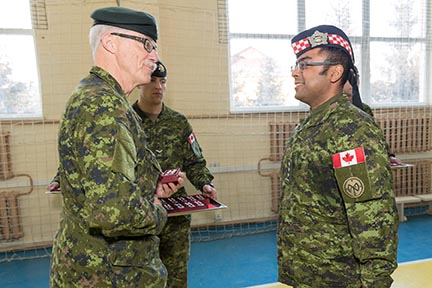 Captain Sarbjit Singh (Rene) Juneja, CD, Infantry Officer, is presented with the Special Service Medal (with NATO bar) by the Colonel of the Regiment, Major General (Retired) J.I. Fenton for deployment on Operation UNIFIER on February 26 in Starychi, Ukraine. Photo: Corporal Neil Clarkson, Joint Task Force - Ukraine. ©2018 DND/MDN Canada.
