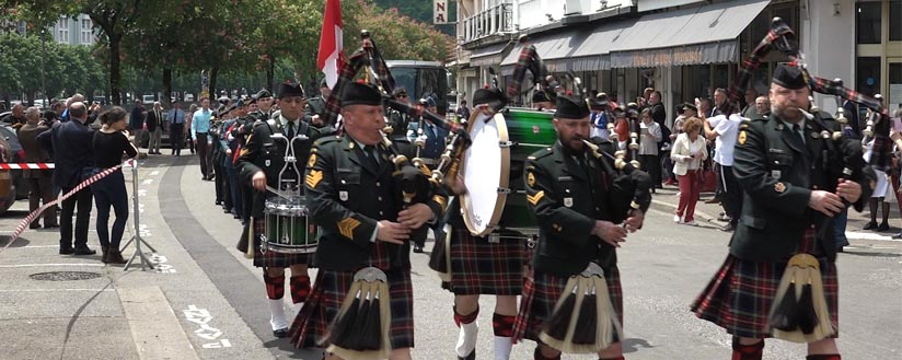 Slide - Pipers and drummers march with a contingent of Canadian soldiers through the streets of Lourdes, France.